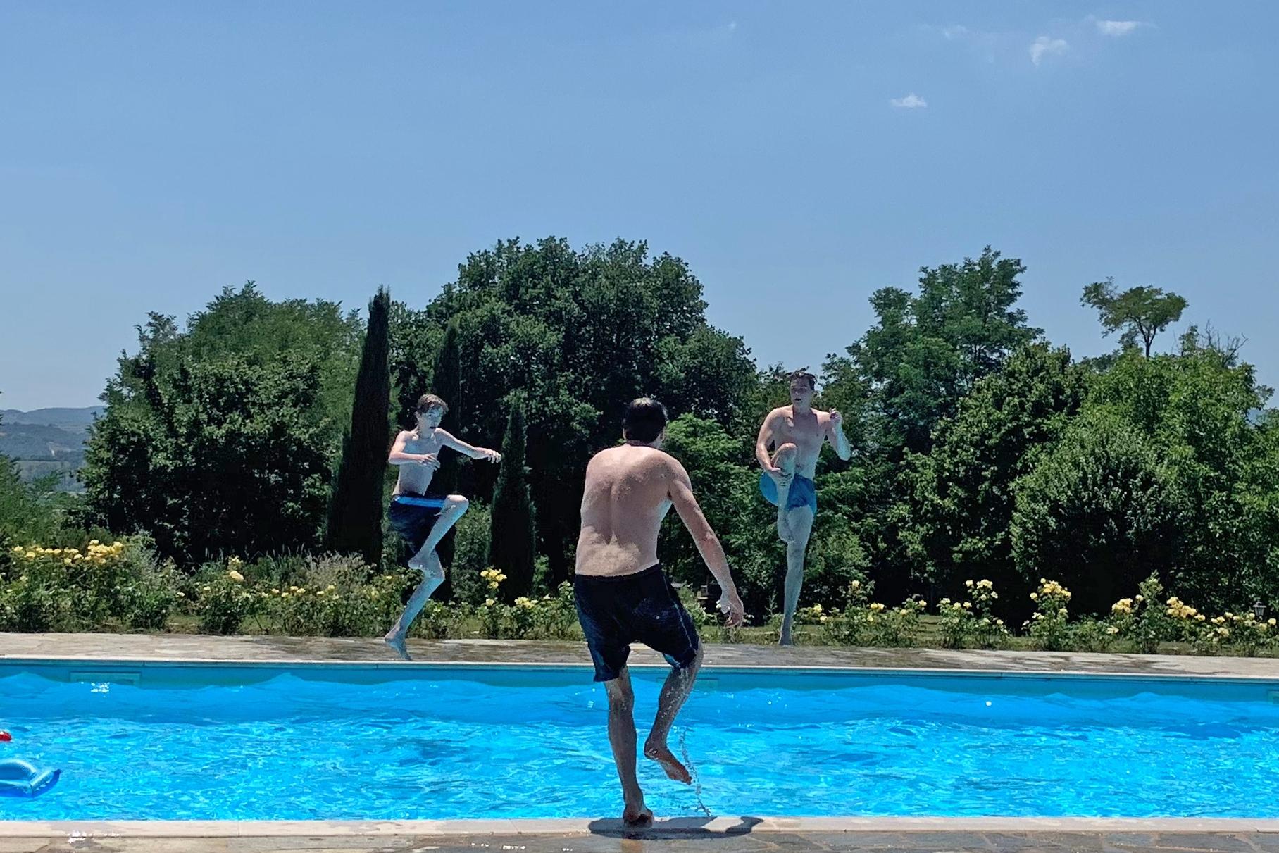 Vater und Söhne beim Sprung in den Pool